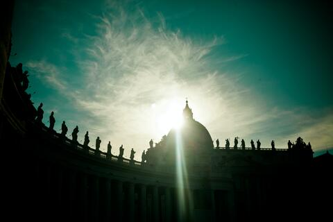 An image of the sun behind the dome in St. Peter's Square, Vatican City
