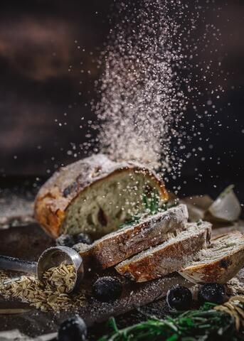 A photo of sliced bread with olives, rosemary, and cardamom pods, with breadcrumbs bursting into the air