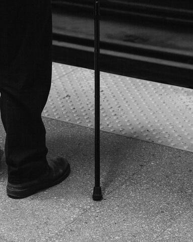 Image of a leg in black pants with a black cane beside it