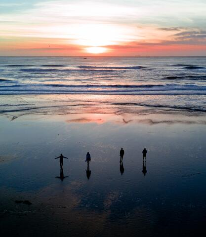A photo of four small silhouetted figures watching a sunrise over water