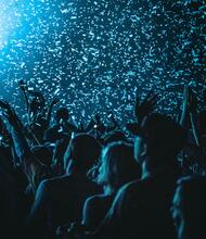 A photo of a crowd waving hands in the air in a burst of confetti