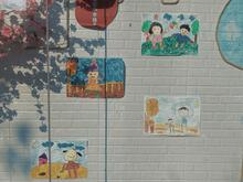 A photo of four children's drawings on a white brick wall