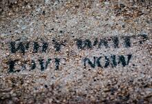 """Image of stenciled text """"WHY WAIT? LOVE NOW"""" in black paint on a gravelly surface"""