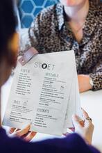 A photo of hands holding a coffeeshop menu